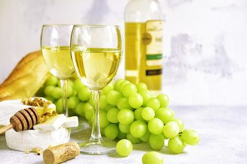 Two glasses of white wine,cheese and grapes.