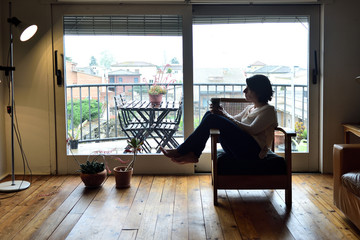 woman sitting in an armchair in front of a window
