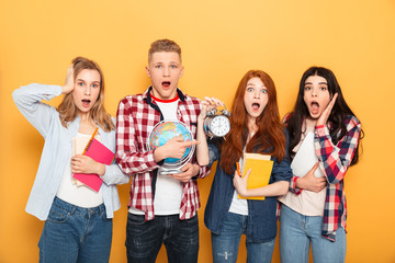 Group of shocked school friends showing alarm clock