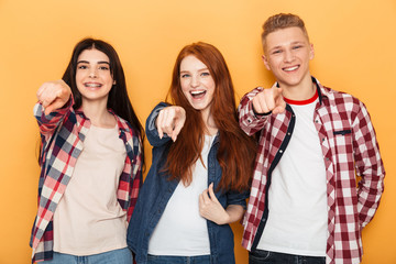 Group of happy school friends pointing fingers at camera