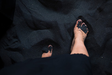 Woman's feet on black sand from above