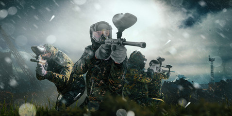 Paintball team in uniform and masks, extreme sport