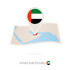 Folded paper map of United Arab Emirates with flag pin of UAE.