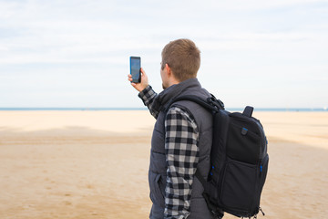 Traveler man taking photos to the beach with smartphone camera on summer travel vacation or hike to the coast.
