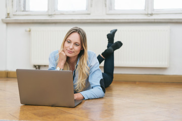 Blonde woman using laptop while lying on floor