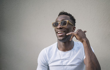 African man wearing white shirt and sunglasses posing.