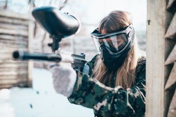Female paintball player with marker gun in hands