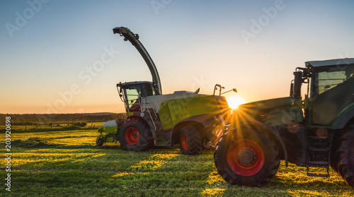 Wall mural Tractor working agicultural machinery in sunny day