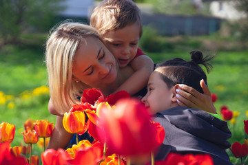 Mother with two sons in the red tulips field