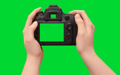 Hands holding dslr camera with empty screen, isolated on green background