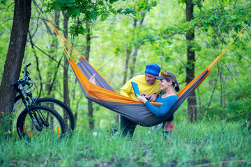 Happy couple relaxes and uses tablet pc in a hammock