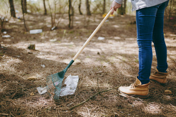 Cropped Young woman in casual clothes cleaning rubbish using rake for garbage collection in littered park. Problem of environmental pollution. Stop nature garbage, environment protection concept.