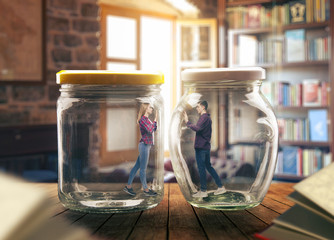 Young couple in big glass jars, loneliness concept