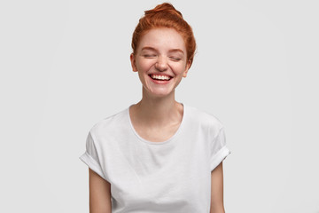 Photo of happy freckled teenage girl with red hair bun, has gentle sincere smile, laughs loyfully at good joke, wears casual white t shirt, poses in studio. Positive emotions and facial expressions