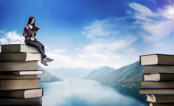 Woman reads while sitting on a mountain of books