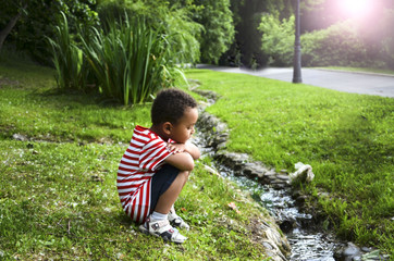 Cute boy sitting by the brook on the nature in the Park and thinks about home