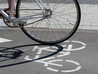 Bike wheel on the background of the sign of the bike road on the asphalt