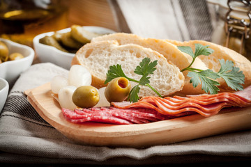 Tapas with sliced sausage, salami, olives, marinated onions, cucumber and parsley on a wooden table.