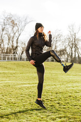 Image of energetic handicapped sportswoman in tracksuit, warming up and raising prosthesis leg on nature