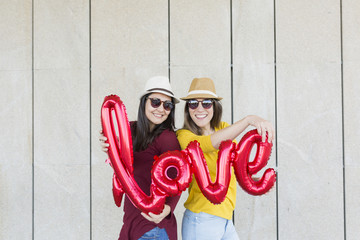 two beautiful young women having fun outdoors with a red balloon with a love word shape. Casual clothing. They are wearing hats and modern sunglasses. LIfestyle outdoors