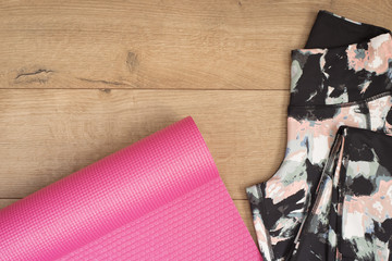 Pink Yoga Mat And Leggings In Flat Lay Style On A Wooden Background. Top View. Fashion Trendy Trainers, Hipster Set. Fitness Concept, Active Lifestyle, Body Care Concept