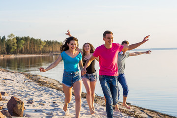Friends are running along the seashore, holding hands and laughing.