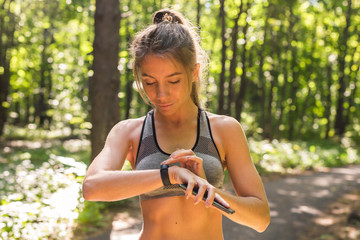 Woman using activity tracker or heart rate monitor. Outdoor fitness concept.