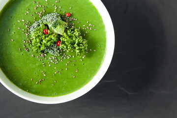 Spinach green soup with broccoli in white bowl top view