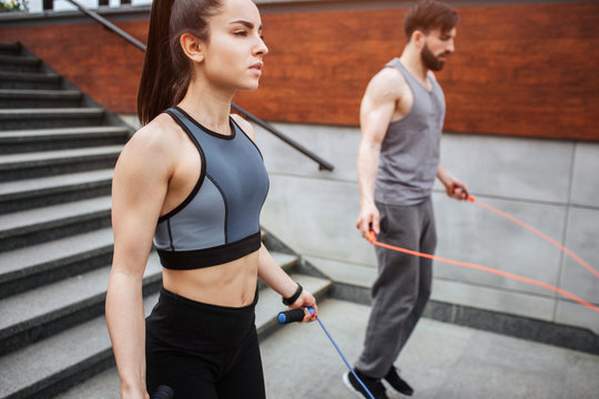 Two strong people are jumping using a rope for that. Guy is jumping more intensive that girl does. He is looking down while she is looking straight forward.