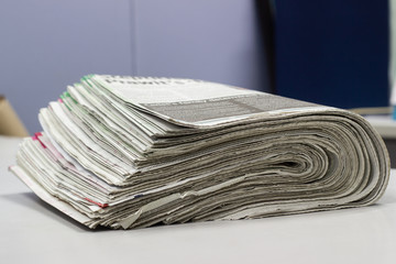 Closeup - Newspaper Stack on white table in work office