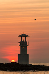 A drone flying next to a silhouette of a lighthouse and a tropical sunset