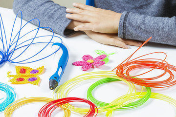 Kid hands and 3d pen, colorful filaments on white desk.