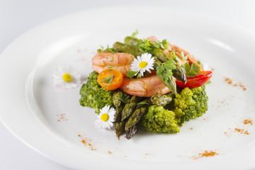 Prawns, asparagus and broccoli with edible daisy flowers. Selective focus.
