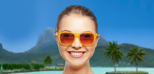 travel, tourism, summer holidays, vacation and people concept - happy young woman or teenage girl in sunglasses over exotic tropical beach background