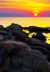reddish sunrise over the sea with rocky shore