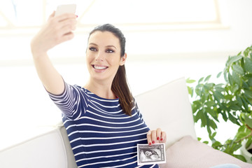Happy pregnant woman making selfie with her 3d ultrasound picture of her baby