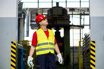 Worker in a factory looking up with machines in the background. Worker wearing reflective west and red helmet