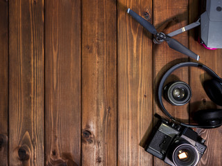 vintage camera and lens with drone and headphones on the wooden surface copy space