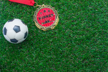 Table top view of soccer or football world cup season background.Flat lay objects gold medal & ball on the artificial green grass wallpaper.Copy space for creative design text and wording content.