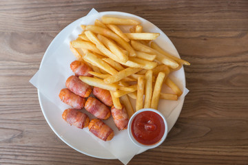 Top view of french fries with ketchup and sausage wrapped in bacon on the wooden table.
