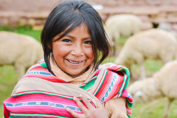 Happy native american girl wearing ethnic aymara cloth. Sheep on the background.