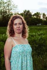 Portrait of a beautiful woman near the field on a farm.