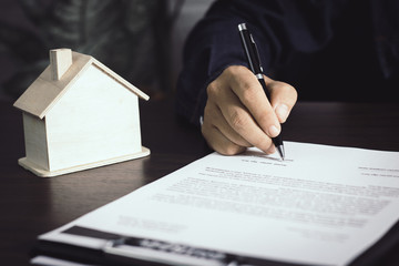 man writing and sign on contract of house after finishing selling and buying home