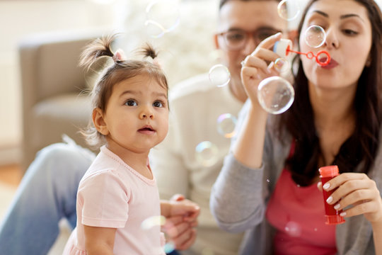 family, childhood and people concept - happy mother blowing soap bubbles and playing with little daughter at home