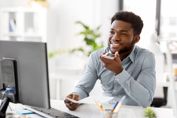 business, communication and technology concept - african americanbusinessman with papers and computer calling or using voice recorder on smartphone at office