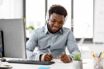 business, technology and people concept - happy african american businessman with headphones and papers listening to music at office