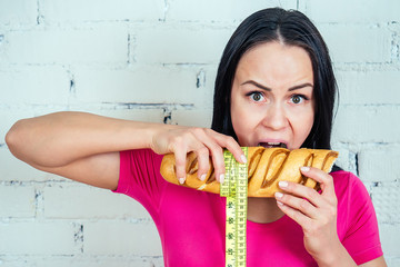 portrait of a beautiful and young woman eating bites a baked high-calorie bread loaf with a yellow measuring tape on a white brick wall background in the gym. fitness concept and diet