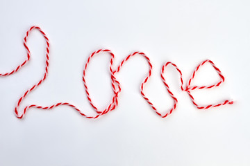 Word love from thread on white background. Inscription love from red and white woolen thread. Valentines Day and love concept.