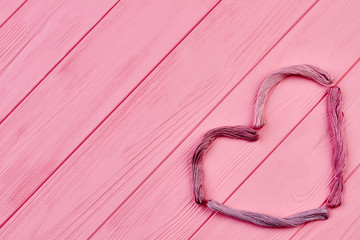 Shape of heart from colorful threads. Pink threads for embroidery arranged in shape of heart and copy space, top view.