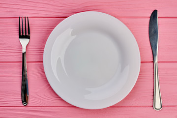 Plate, fork and knife on table. Pink textured wood with white plate, silver fork and knife, top view.